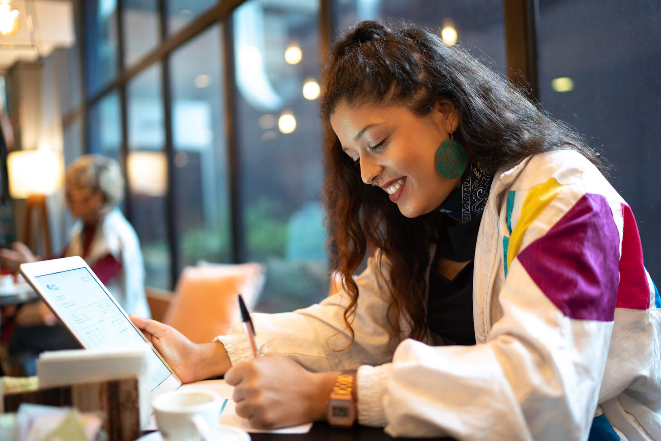 Young woman smiling as she writes down notes while holding an iPad